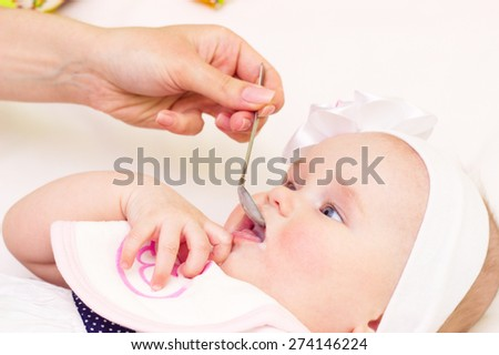 Young mother is feeding her baby at room - stock photo