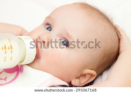 Young mother is feeding her baby at room