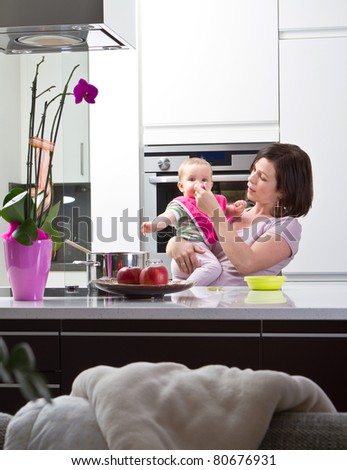 Young mother is feeding her baby in a modern kitchen setting.
