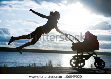 young mother is flying in stroller with a baby at sunset