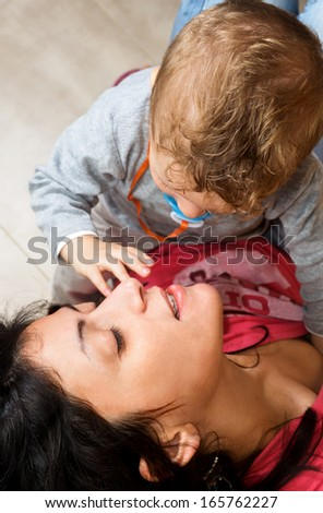 Young mother is holding her baby playing tenderly