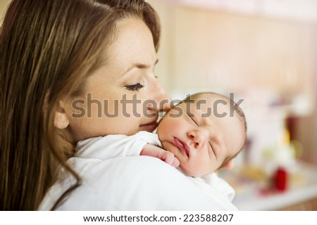 Young mother is holding her cute newborn baby girl