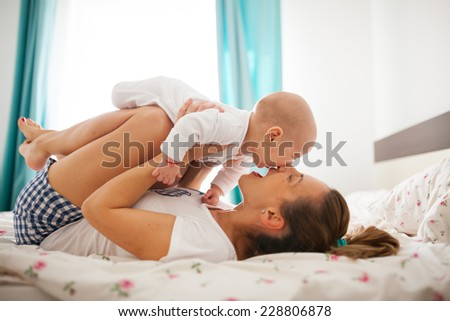 Young mother is playing with her baby boy in bed - stock photo