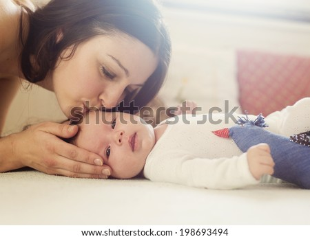 Young mother is playing with her little baby - stock photo