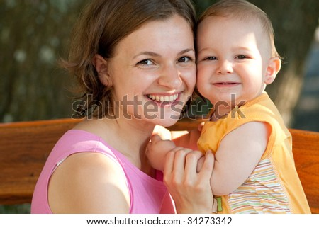 Young mother is sitting on bench with her cute baby