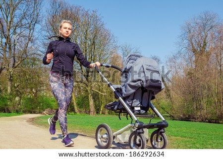 Young mother jogging with a baby buggy - stock photo