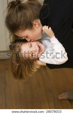 Young mother kisses her little girl. - stock photo