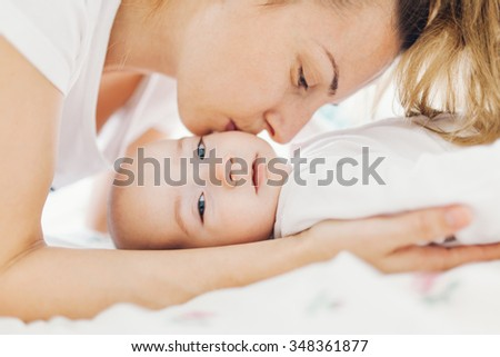 Young mother kissing her adorable baby boy on cheek