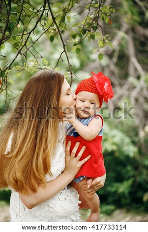 Young Mother Kissing Her Cute Baby in Funny Red Hat