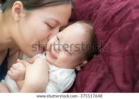 Young mother kissing her little happy baby - stock photo