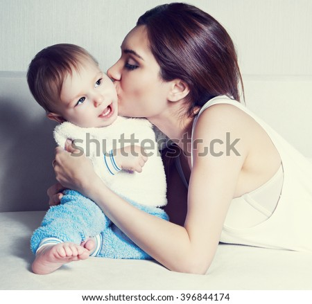 young mother kissing her one year old baby at home - stock photo