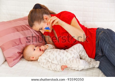 Young mother laying on sofa and playing with baby