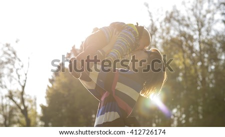 Young mother lifting her baby in the air giving him or her a kiss lit by bright sun outside in nature.