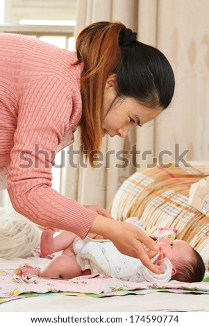 Young Mother Looking After Her Newborn Baby - stock photo