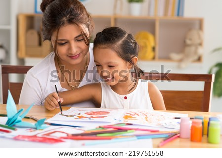 Young mother looking how her daughter drawing a picture - stock photo