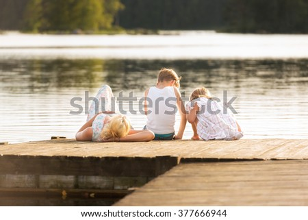 Young mother lying on a jetty while her two kids playing together and watching something in the water. Quiet, dreamy atmosphere and typical Nordic Light
