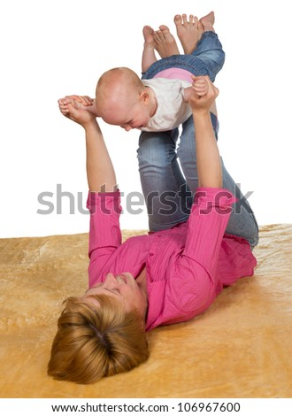 Young mother lying on her back on the floor playing with her baby which is balanced on her raised legs with its arms outstretched - stock photo