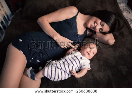 Young mother lying with her newborn baby on bed - stock photo