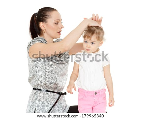 Young mother making hairstyle (ponytail) of the small daughter on a white background. - stock photo