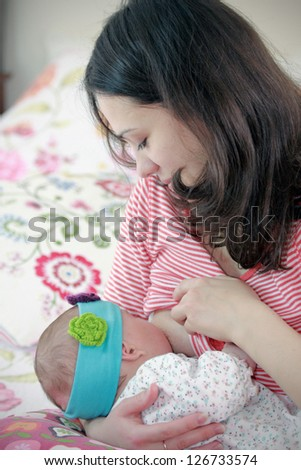 Young mother nursing her newborn daughter - stock photo