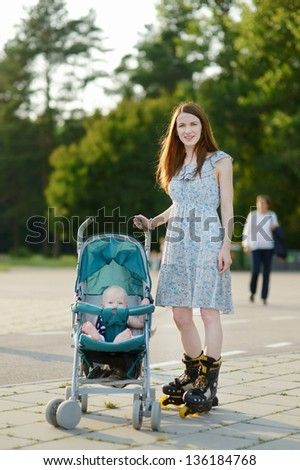 Young mother on roller skates with baby stroller - stock photo