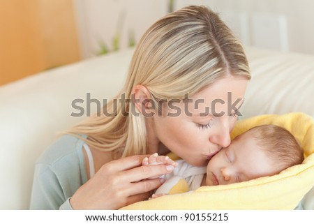 Young mother on the sofa kissing her baby - stock photo