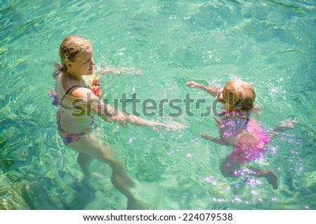 Young mother play with adorable daughter to relax in crystal clear laguna on tropical island - stock photo