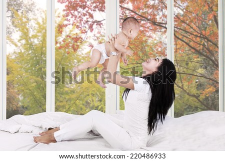 Young mother playing on bed with her baby at home in autumn