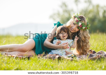 young mother playing with baby girl outdoors in summer park. Mother and baby. woman with daughter having fun together. Mother and baby in park portrait