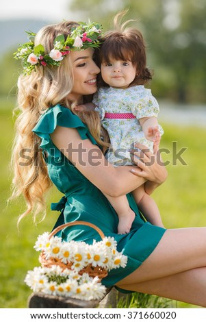 young mother playing with baby girl outdoors in summer park. Mother and baby. woman with daughter having fun together. Mother and baby in park portrait - stock photo