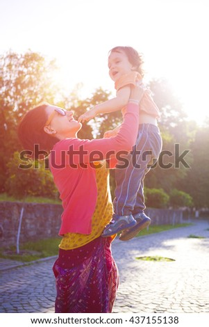Young mother playing with baby in the Park and throws it up. - stock photo