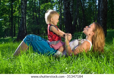 Young mother playing with  daughter on grass - stock photo