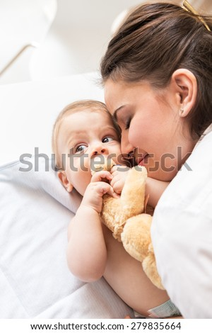 Young mother playing with her baby boy.