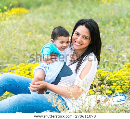 young mother playing with her baby boy on the meadow in sunny  day - stock photo