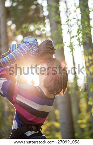 Young mother playing with her baby lifting the child high in the air with a sun burst and flare filtering through backlighting them from behind. - stock photo