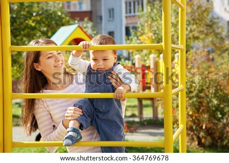 young mother playing with her baby on the playground. Mom and son