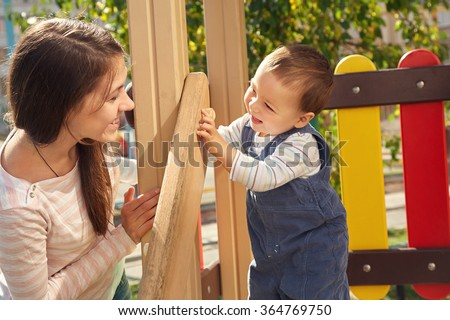 young mother playing with her baby on the playground. Mom and son - stock photo
