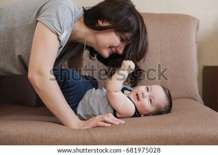 Young mother playing with her baby son on a sofa at home in a lovely happy smiling portrait with the infant laughing and gurgling with pleasure