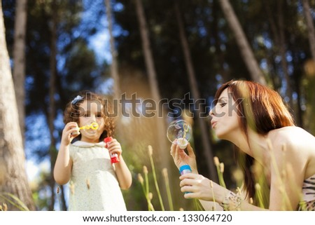 Young mother playing with her child in nature - stock photo