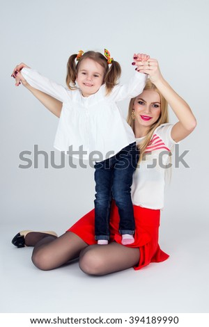 Young mother playing with her daughter - stock photo