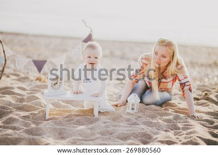 Young mother playing with her little son at the beach - stock photo