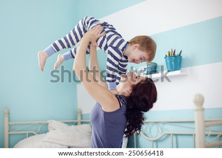 Young mother playing with her 2 years old little son at the bedroom - stock photo