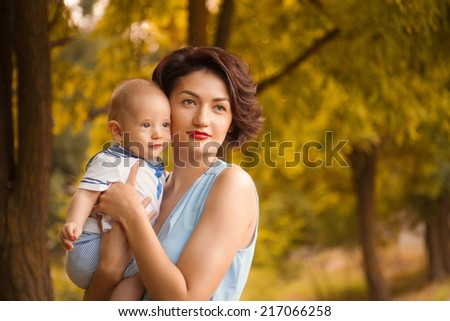 Young mother playing with little baby boy  outdoors on a summer day - stock photo