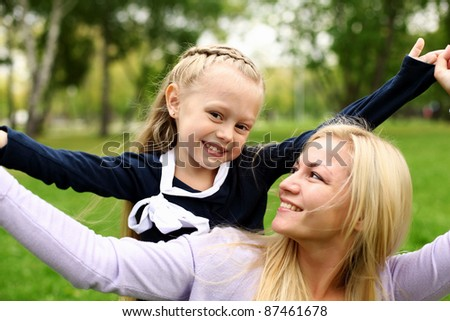Young mother playing with little daughter in green summer park - stock photo