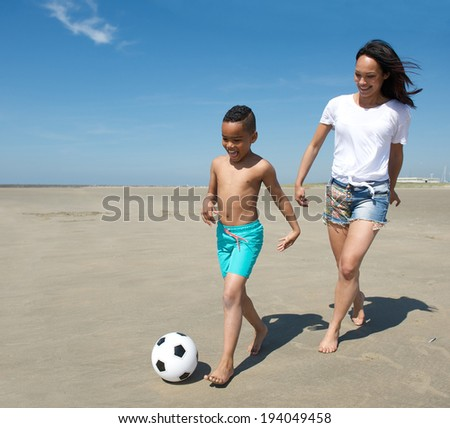 Young mother playing with son on the beach in summer - stock photo