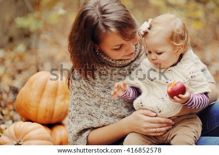 young mother plays with the native daughter in a warm knitted sweater in autumn park near pumpkin