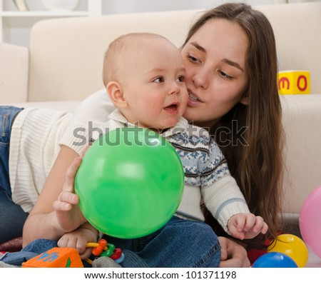 young mother plays with the small son of the house