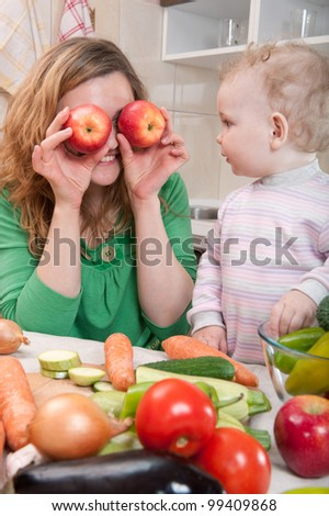 Young mother preparing fresh vegetable salad with her baby daughter - stock photo