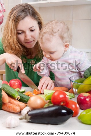 Young mother preparing fresh vegetable salad with her baby daughter