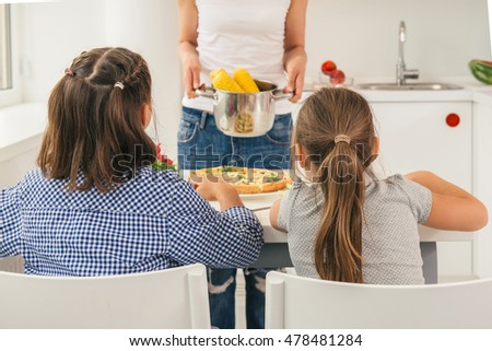 Young mother preparing tasty corn for her daughters. Concept healthy lifestyle in modern family